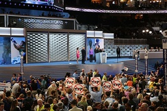 A group of delegates on the convention floor hold up signs in protest of the Trans-Pacific Partnership.