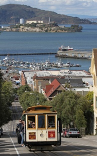 A cable car ascending Hyde St, with Alcatraz on the bay behind