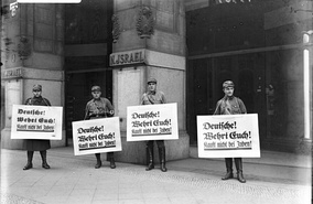 "Nazi boycott of Jewish businesses: SA troopers urge a boycott outside the Nathan Israel Department Store, Berlin, 1 April 1933. All signs read: ""Germans! Defend yourselves! Don't buy from Jews.""[67]"