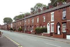 View down a street of two-storey brick-built terraced houses.