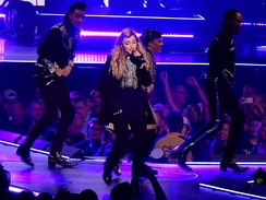 Madonna singing on a blue-lit stage in black costumes, surrounded by dancers