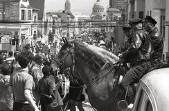 A pair of police officers mounted on horses observe a protest march down a street in San Francisco.