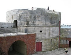 A front facing view of Portsmouth's Round Tower, which once guarded the entrance to Portsmouth Harbour. The Round Tower itself is made of stone and has a large circular base.