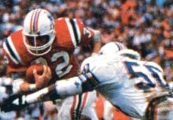 Craig James (left) rushes the ball past the Dolphins' defense in the 1985–86 AFC Championship game.