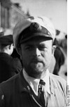 A bearded man wearing a white peaked cap, and an Iron Cross displayed at the front of his uniform collar.