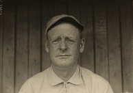 A black and white head shot of a man in a baseball cap.