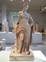 Left, a Macedonian funerary stele, with an epigram in Greek, mid-4th century BC, Vergina. Right, marble cult statue of Aphrodite Hypolympidia, dated 2nd century BC, from the sanctuary of Isis at Dion, Pieria, Central Macedonia, Greece, now in the Archaeological Museum of Dion.