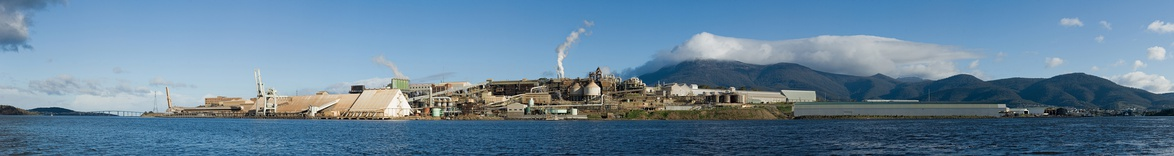 A panorama featuring a large industrial plant on a sea side, in front of mountains.