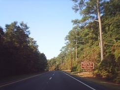 One direction of a divided highway passing through a forest with a brown sign stating Pocomoke River State Park Shad Landing is the next right turn