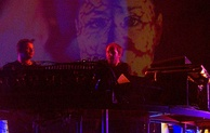 A dark image of two men in the back playing the synthesizers.