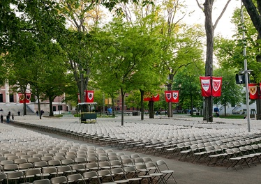 Seating for degree candidates in Tercentenary Theatre, with banners displaying arms of the various graduate and professional schools, and upperclass houses. Beyond the trees are the columns of Widener Library.