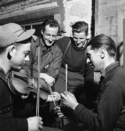 Québécois lumberjacks playing the fiddle, with sticks for percussion, in a lumber camp in 1943.