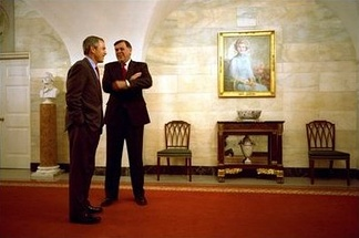 Senator Mel Martínez chats with U.S. President George W. Bush in the Center Hall of the White House during a celebration of Cinco de Mayo. The official portrait of former First Lady Betty Ford can be seen on the wall.