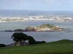 Northeastward view of Plymouth Sound from Mount Edgcumbe Country Park in Cornwall, with Drake's Island (centre) and, behind it from left to right, the Royal Citadel, the fuel tanks of Cattedown, and Mount Batten; in the background, the hills of Dartmoor.
