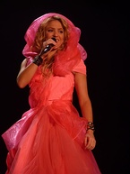 A lady is singing a song dressed in a hooded fuchsia gown. She has a mic in her hand.