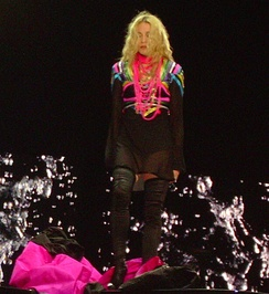 A blond woman standing onstage. Her wavy hair falls on her face. She wears a short black kaftan, a number of pink threads around her neck and long black boots. Near her feet a pink and black cloth is billowing. Behind her, image of water splashing is visible on screen.