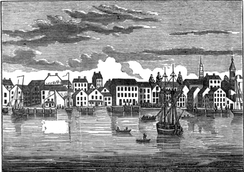 Drawing or etching of quiet river port with many boats and many three-story buildings along water's edge
