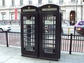 Two black K6 telephone boxes in Piccadilly in the City of Westminster, operated by New World Payphones Ltd