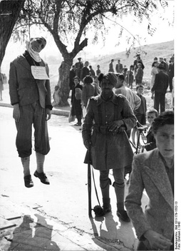 The body of a hanged man, guarded by a man of the collaborationist Security Battalions, in public view, Greece 1943