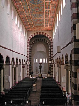 The interior of another long narrow church with high windows. The arch leading into the chancel at the far end has alternating red and white stones.