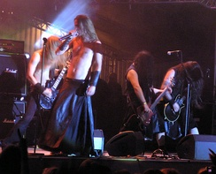 Four long haired musicians perform on a small stage in the spotlight, long hair swinging. The singer, wearing a black leather floor-length skirt, and the bass guitar player are bare chested with black leather wrist bands. The two other guitar players are in sleeveless black shirts, one with knee-length jeans and the other with black wrist band. Amplifiers crowd the stage.