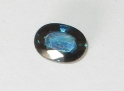Dark blue sapphire, probably of Australian origin, showing the brilliant surface luster typical of faceted corundum gemstones.