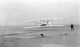 First flight of the Wright Flyer I, December 17, 1903, Orville piloting, Wilbur running at wingtip.
