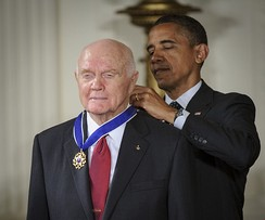 Barack Obama putting on Glenn's Medal of Freedom from behind