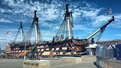 A picture of HMS Victory, the world's oldest commissioned naval ship, situated in Portsmouth's dry dock. The ship itself is missing its figurehead in this photo, but retains its original sails.