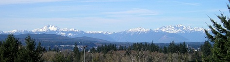 The Olympic Mountains in winter, as seen from the east. The Brothers is the large double peak on the left, and Mount Constance is on the right.
