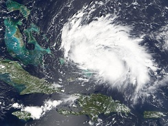 Satellite image of a rather weak tropical cyclone - the storm is an elongated mass of clouds, stretching horizontally.
