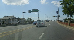 Westbound view on U.S. 50, Ocean Gateway, leaving Ocean City. Sign over Eastbound lane displays distance to Sacramento, California, 3,073 miles.