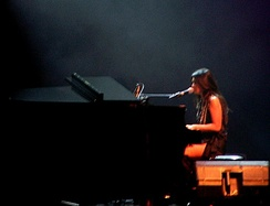 Anggun playing piano during her 2006 concert in Bandung, Indonesia.
