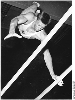 A gymnast performing on the parallel bars in 1962.