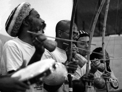 Three berimbau players