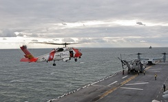 A U.S. Coast Guard helicopter preparing to land on the flight deck of the amphibious assault ship USS Wasp (LHD-1)