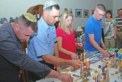 US Navy personnel light candles on Hanukkah