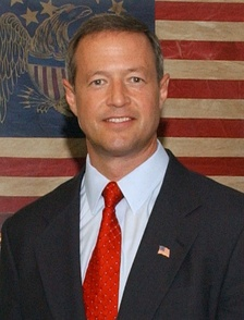 A Caucasian male in a black suit with a light blue shirt and a red tie smiles while standing in front of an American flag.