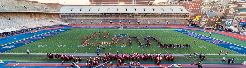 "The University of Pennsylvania Band and alumni spell ""Penn"" on the field during the Homecoming game in November 2019. Note the south and east stands are empty because they are undergoing renovation."