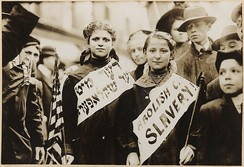 "Two girls wearing banners in Yiddish and English with the slogan ""Abolish child slavery!!"" at the 1909 International Workers' Day parade in New York City"