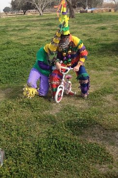 "Two Mardi Gras ""stealing"" a child's bicycle at the South Cameron Courir"