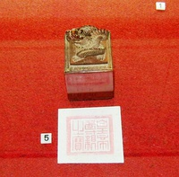 Seal, decorated with a dragon, and its imprint against a red background