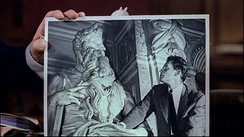DeMille holds a photograph of Charlton Heston looking at Michelangelo's Moses. Heston's resemblance to the sculpture helped him win the role of Moses.[18]