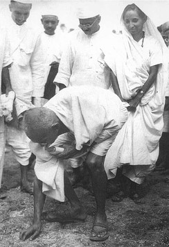Gandhi picking salt during Salt Satyagraha to defy colonial law giving salt collection monopoly to the British.[251] His satyagraha attracted vast numbers of Indian men and women.[252]