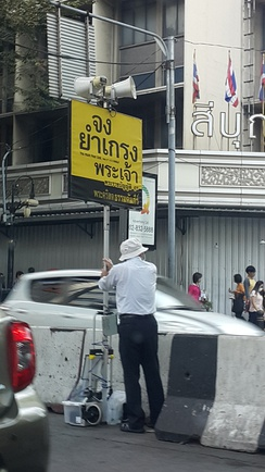 A man holding the sign persuading people to read Bible in Thai at Sala Daeng BTS Station, Bangkok