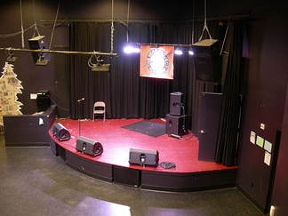 "This small venue's stage shows an example of a typical monitor speaker set-up: there are three ""wedge"" monitors directed towards the area of the stage where singers and instrumentalists will be performing. The drummer has both a subwoofer cabinet (for monitoring the bass drum and the electric bass) and a ""wedge""-style cabinet for monitoring vocals and mid- or high-frequency sounds."
