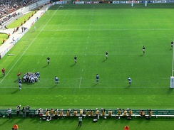 The forwards are in the scrum while the backs are lined up across the field.