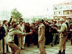 A protester giving flowers to an army officer