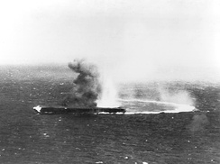 Shōkaku, at high speed and turning hard, has suffered bomb strikes and is afire.