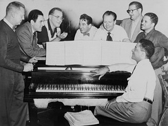Goodman (third from left) in 1952 with some of his former musicians, seated around the piano (left to right): Vernon Brown, George Auld, Gene Krupa, Clint Neagley, Ziggy Elman, Israel Crosby and Teddy Wilson (at piano)